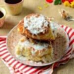 um prato com pao de coco e xicaras de cafe ao lado