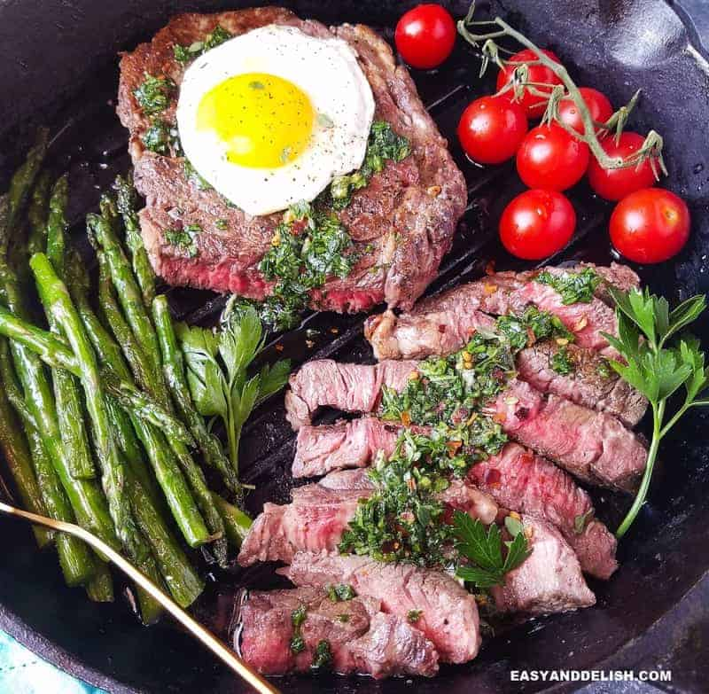 bife a cavalo parcialmente fatiado com um ovo por cima e verduras ao lado