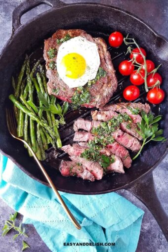 Steak and eggs in a pan with sauce on top and veggies on the side