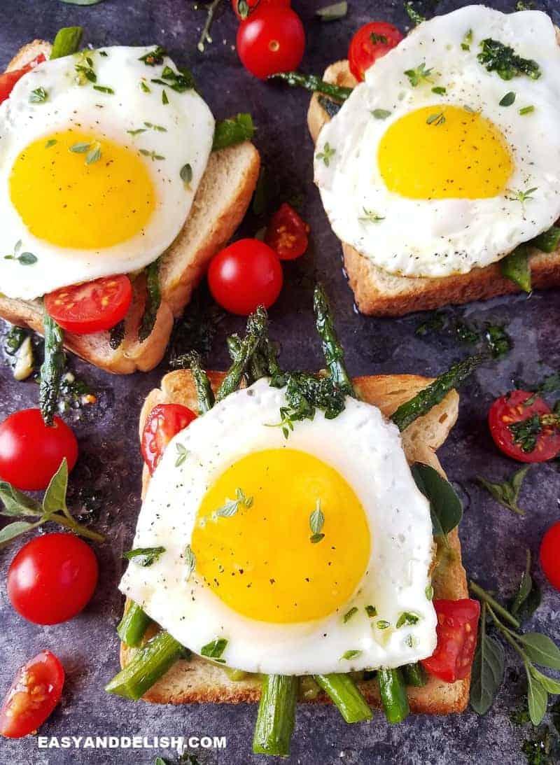 3 ovos fritos por cima de torradas com vegetais ao lado