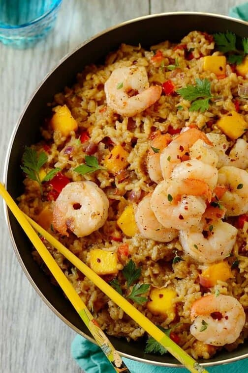 shrimp fried rice in a skillet with chopsticks on the side