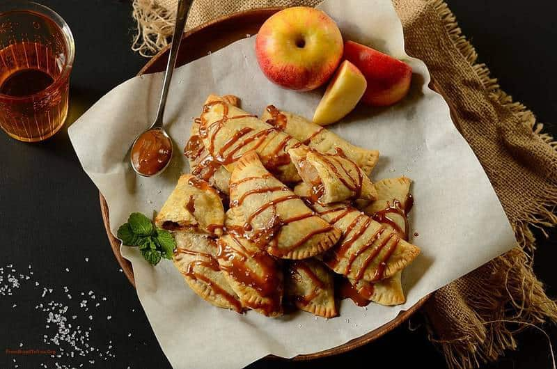 Dulce de Leche Apple Hand Pies in a platter with apple slices on the side