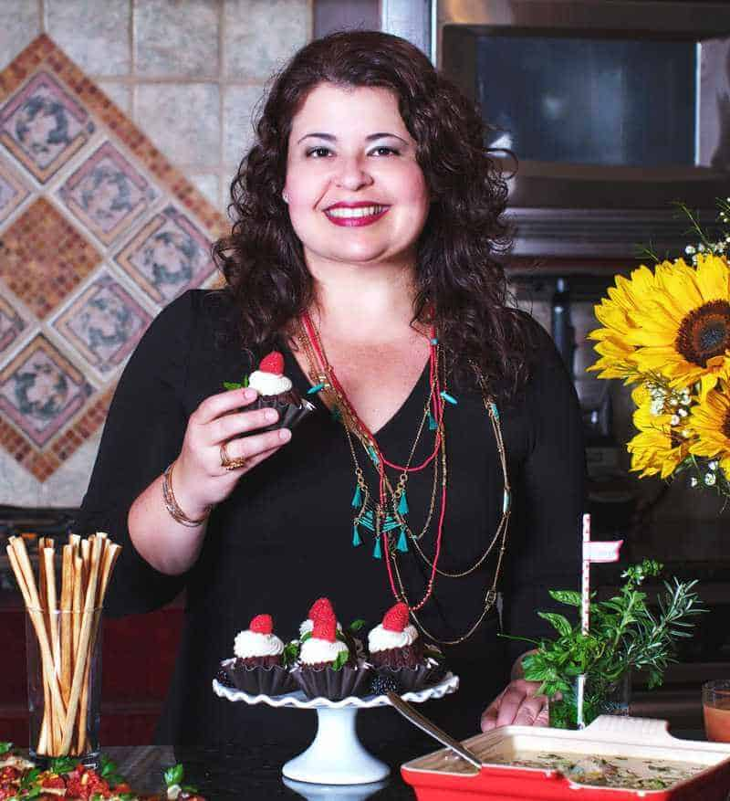 blog author in the kitchen holding a cupcake