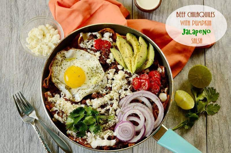 breakfast chilaquiles in a skillet with silverware and garnishes on the side