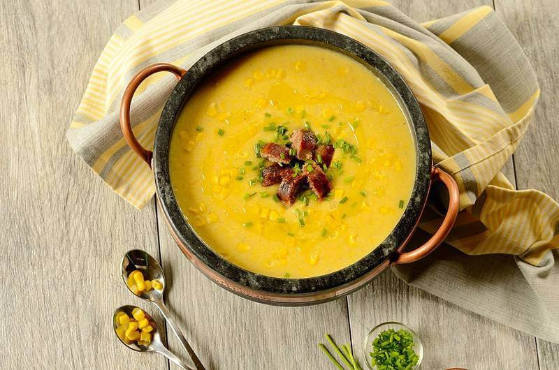 Brazilian corn chowder or sopa de milho verde in a stone cooking crock