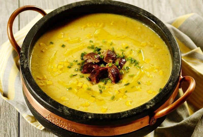 a pot of corn chowder with chopped sausage on top as one of the 70 easy one pot meals