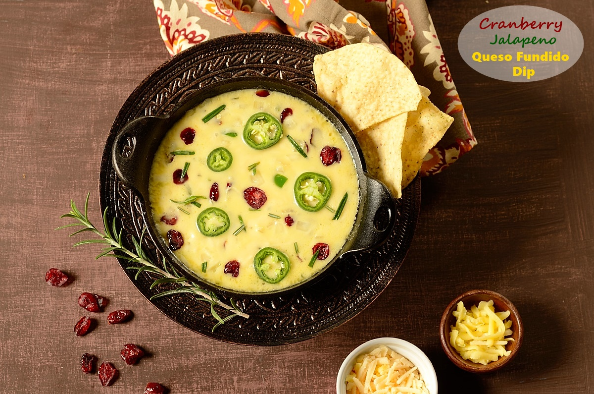 a skillet of queso fundido topped with jalapeno and dried cranberries and chips on the side