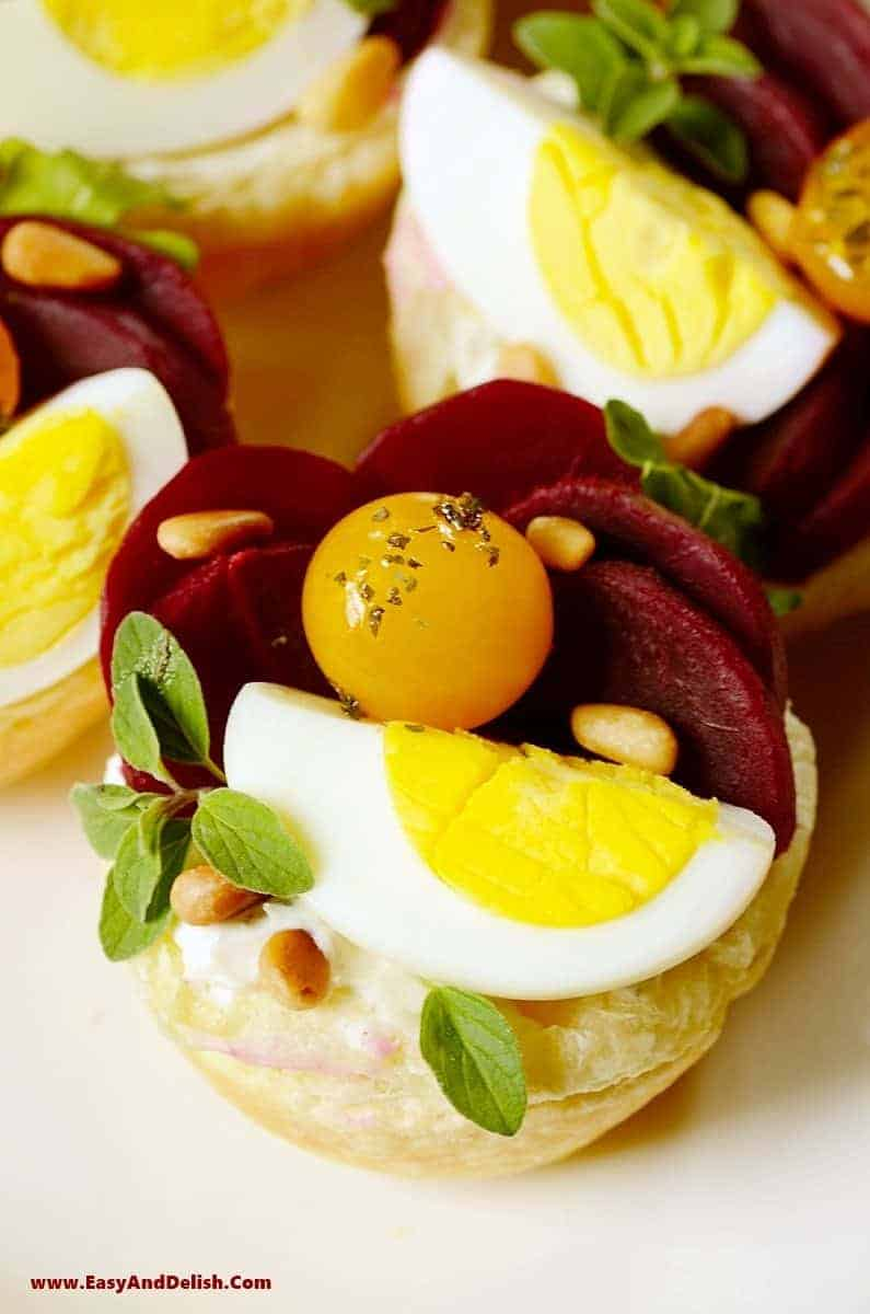 a close up of tartlets topped with boiled eggs, beet slices, and cherry tomatoes