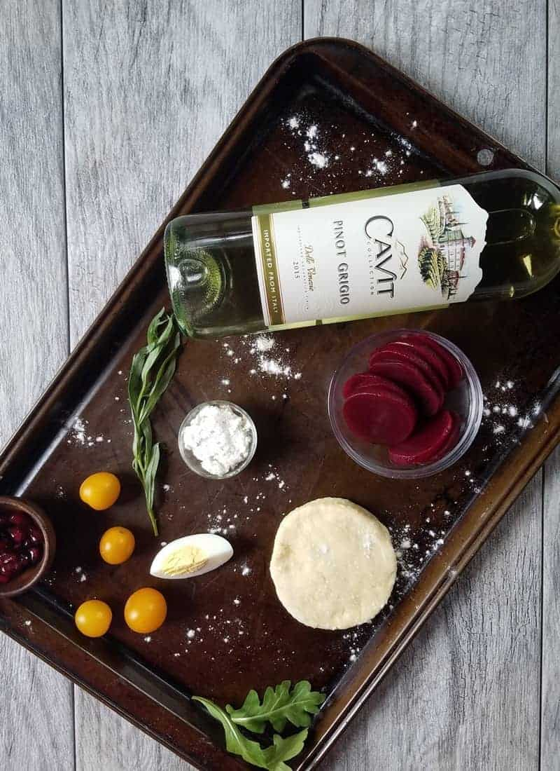 A baking sheet with a bottle of wine and ingredients for the tartlets
