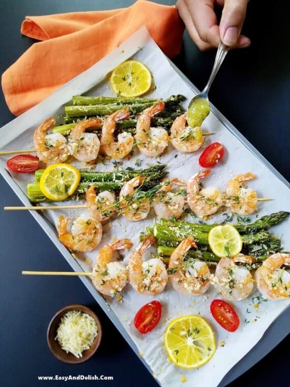 drizzling sauce over baked shrimp and asparagus