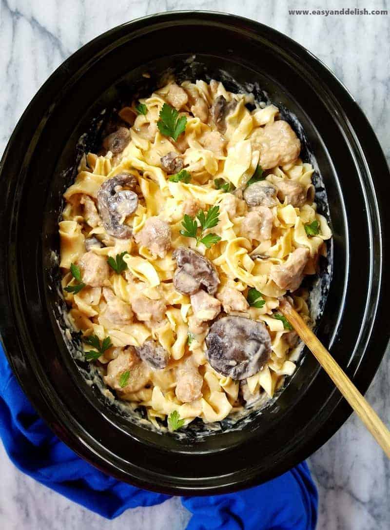 pork stroganoff over noodles in a slow cooker bowl