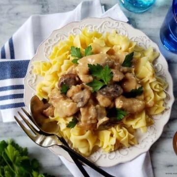 slow cooker pork stroganoff over egg noodles in a plate