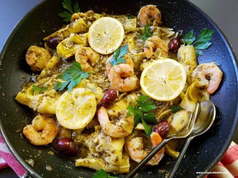 close up image of one pot seafood in pesto sauce with lemon slices on top