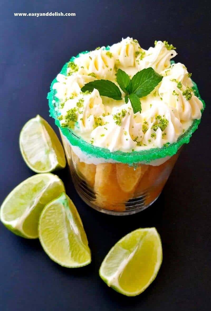 close up of coconut tiramisu in a glass with lime wedges