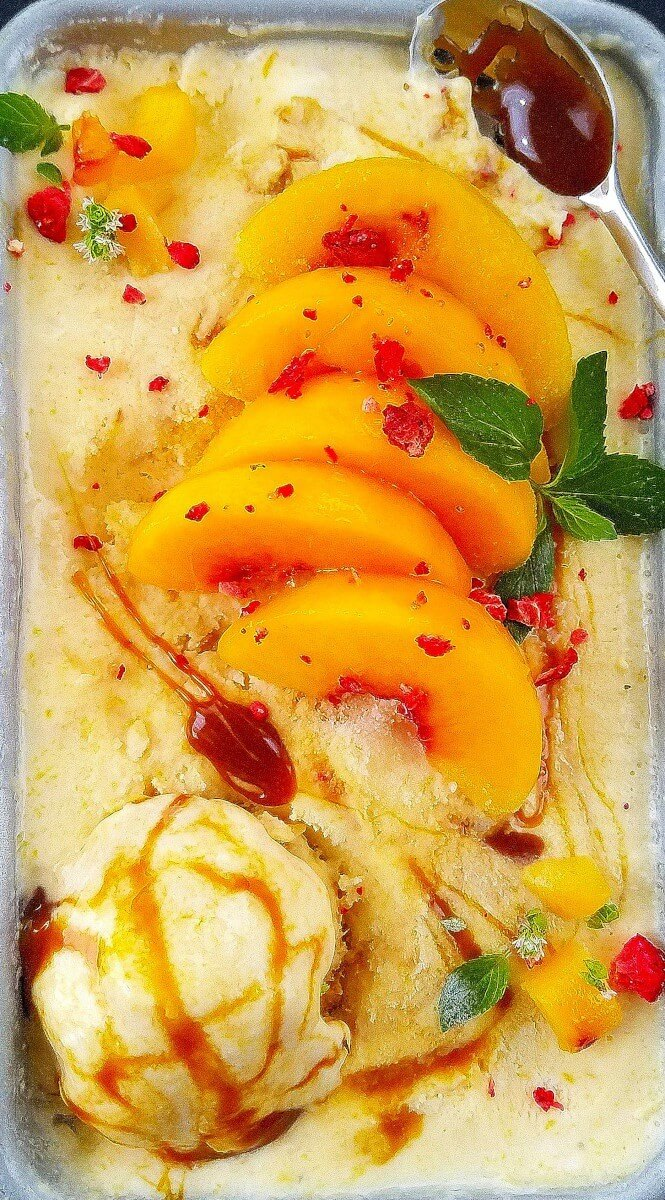 close up of peach nice cream topped with peaches and drizzled with caramel
