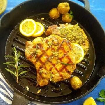 A pan of grilled pork chops with Chimichurri plus mini potatoes