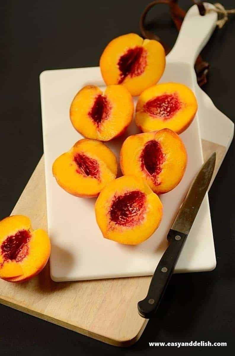 peach halves on a cutting board with a kinfe