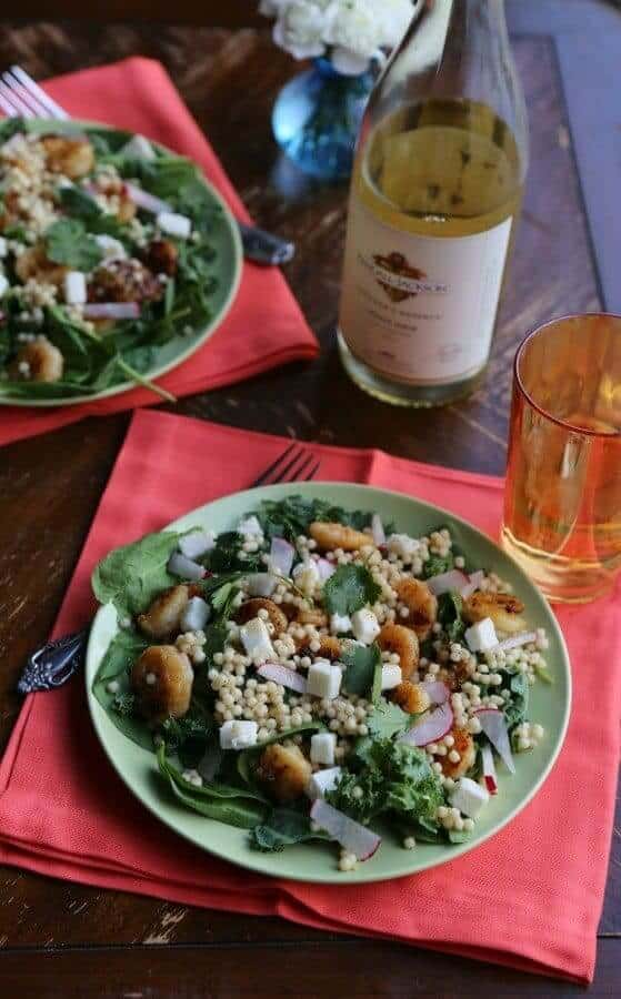 couscous salad in a plate with a  bottle of wine on the background