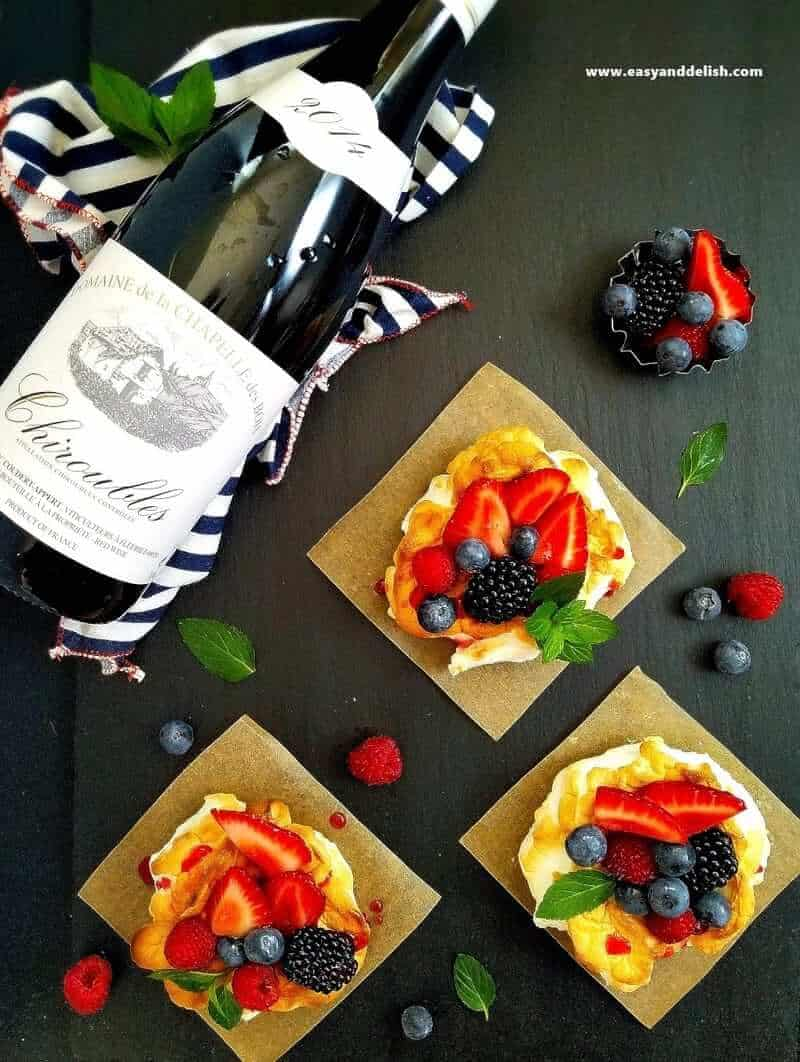 a bottle of wine and 3 cloud eggs with berries