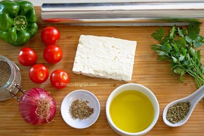 Food on a wooden cutting board, with Feta and other ingredients