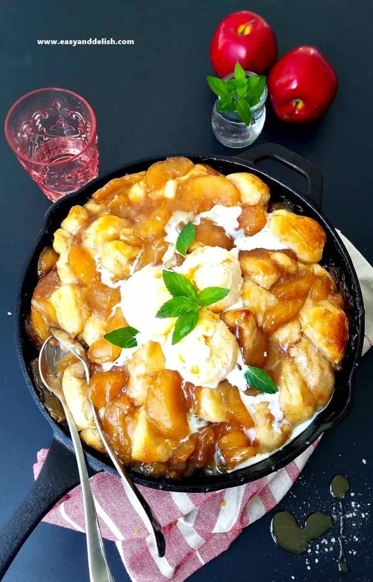 slated caramel apple cobbler in a skillet topped with ice cream