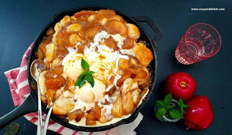apple cobbler in a skillet topped with ice cream