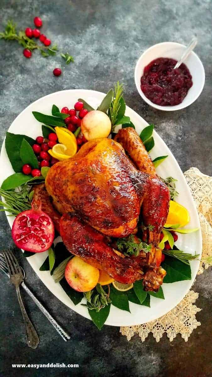 brined roast turkey in a platter garnished with fruits for Thanksgiving