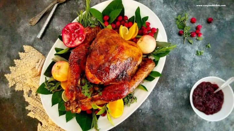 whole turkey in a platter with leaves and fruits around plus sauce on the side