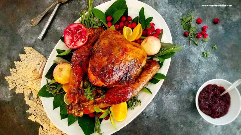 roasted turkey in a platter with leaves and fruits around plus sauce on the side