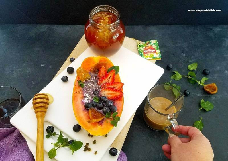 papaya boats with a cup of coffee and a jar of honey