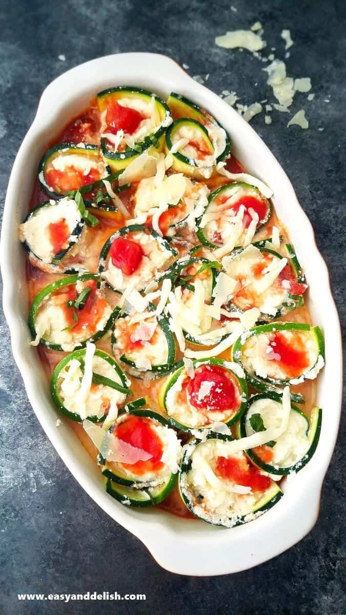 Image of baked caprese zucchini roll ups in a baking dish right before being baked.