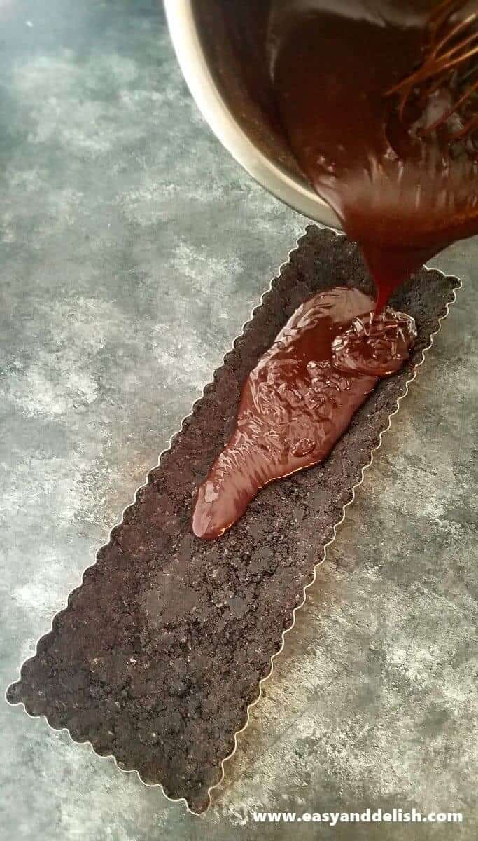 Image of nutella filling being poured into the baking pan over the Oreo crust