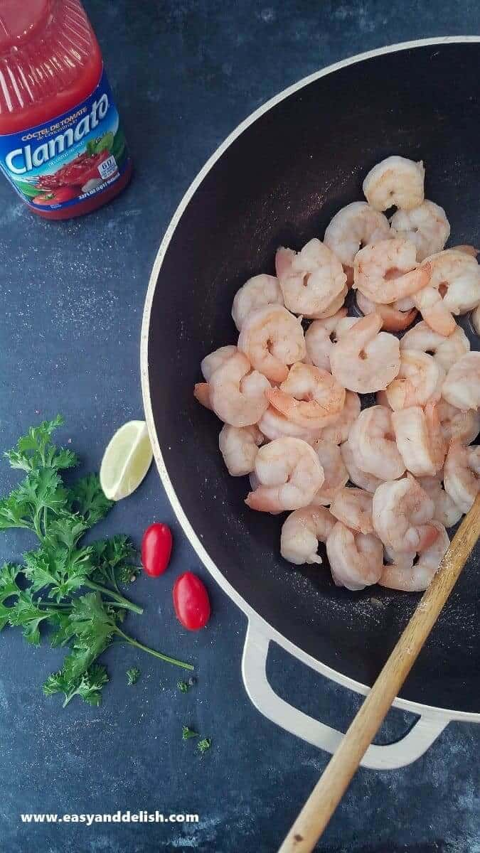 Image of a pan containing sauteed shrimp -- with lime, vegetables, and Clamato juice near the pan.