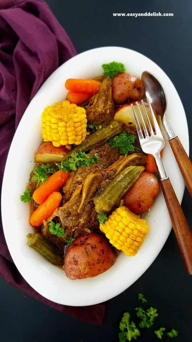 A platter full of Instant Pot Beef Short Rib Pot Roast with Vegetables with a spoon and fork on the side.