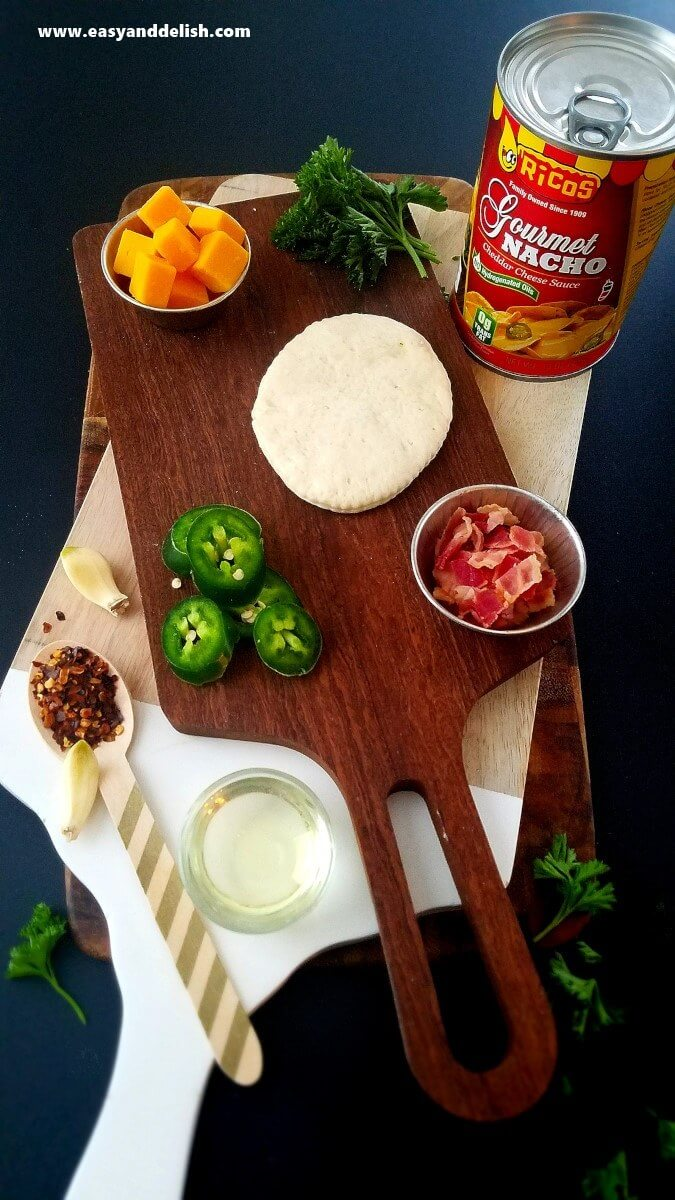 Image displaying ingredients of nacho pizza bombs over cutting board.