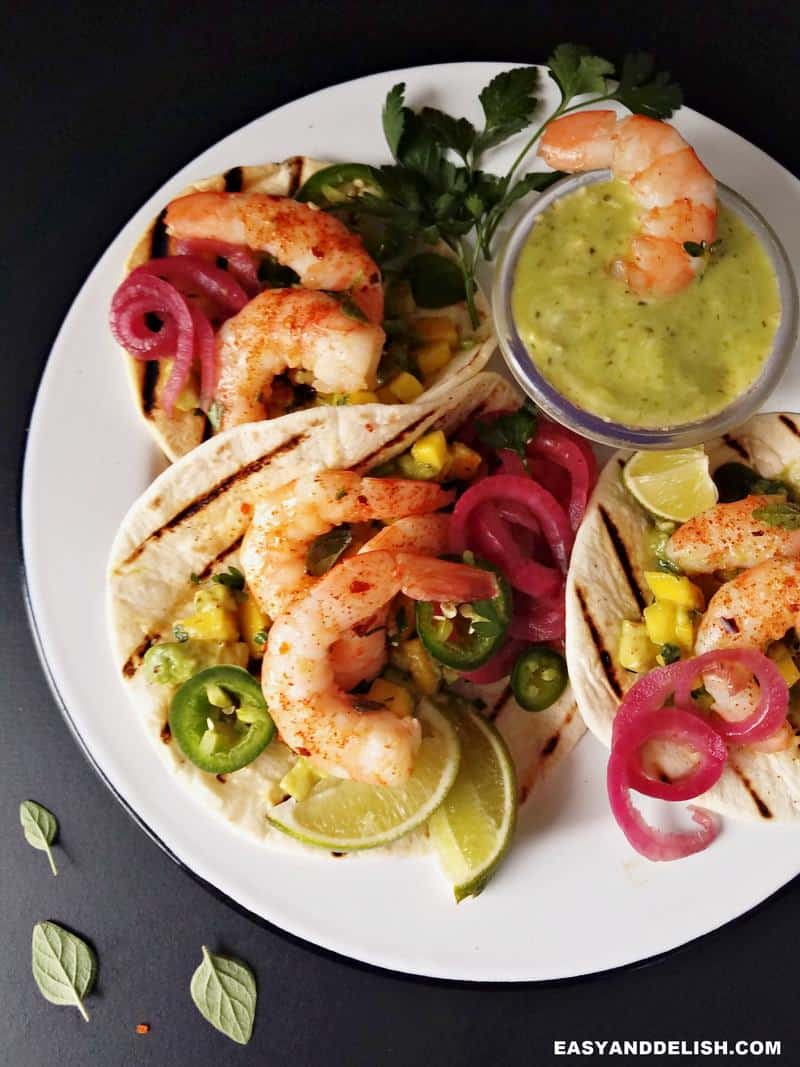 spicy shrimp tacos in a plate with side