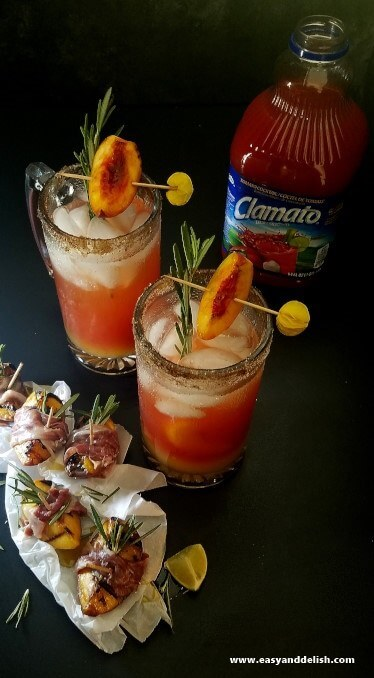 Two beer glass mugs filled with peach rosemary michelada between a bottle of juice and skewers of peach wrapped with prosciutto.