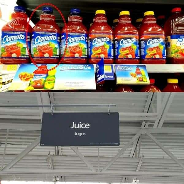 Walmart shelf with bottles of Clamato tomato juice and a juice aisle sign.