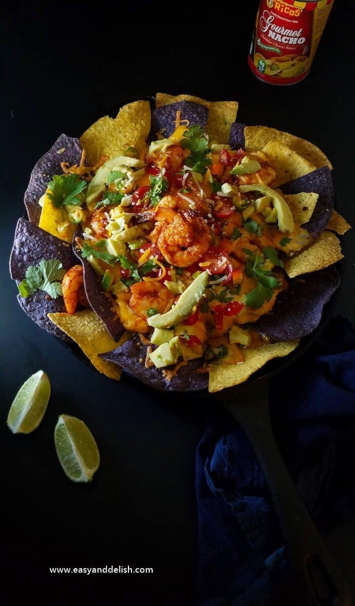 Overhead view of shrimp nachos on a skillet between lime wedges and a can of nacho sauce.
