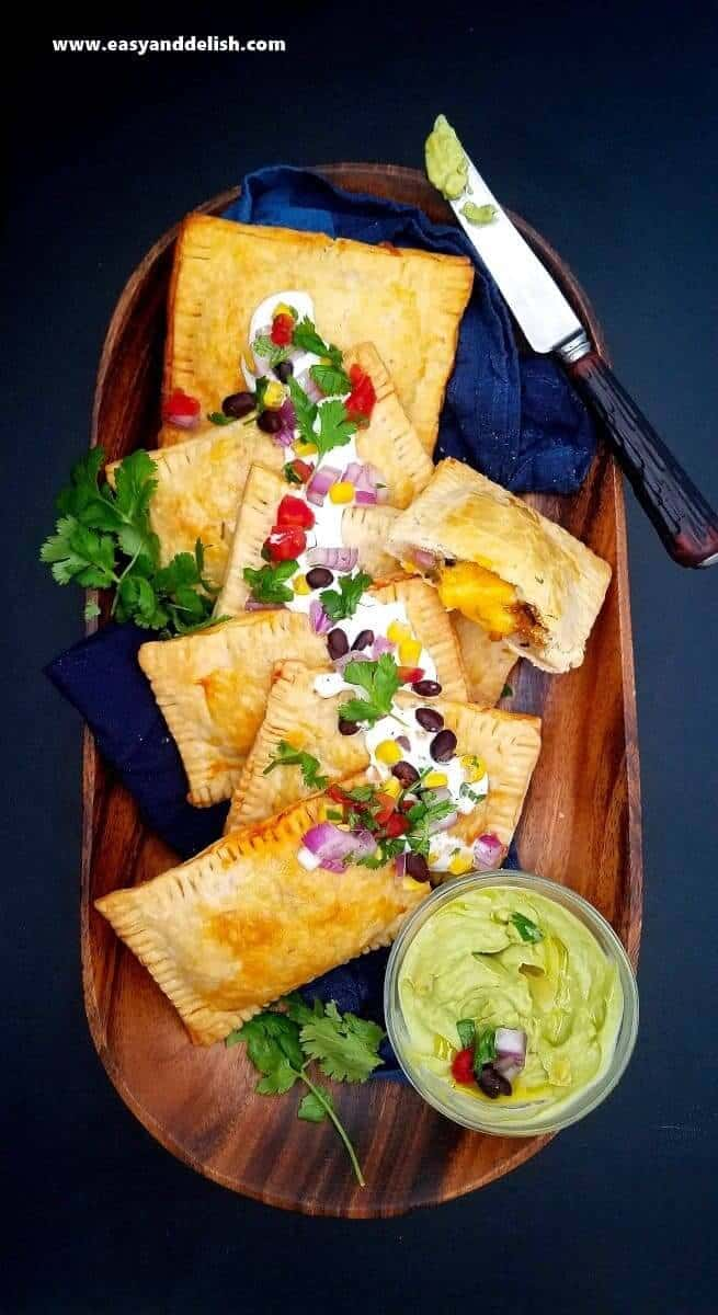 Overhead view of a wood platter full of Southwestern Taco Hand Pies with a small bowl of guacamole and a knife on the side.