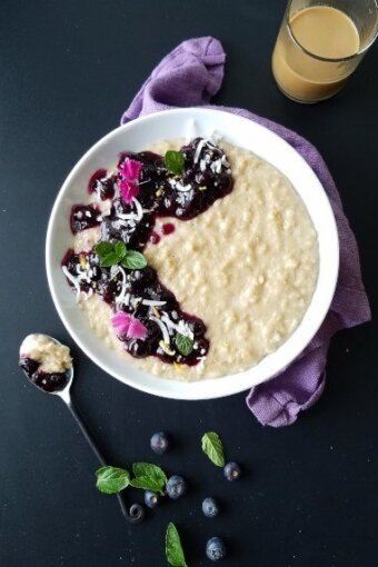 A bowl of coconut oatmeal pudding topped with blueberry sauce