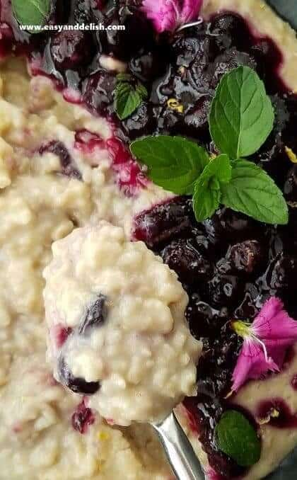 Overhead shot of a spoon full oatmeal above a bowl of oatmeal topped with blueberry sauce.