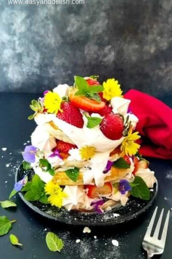 a pile of strawberry pancakes garnished with berries and flowers