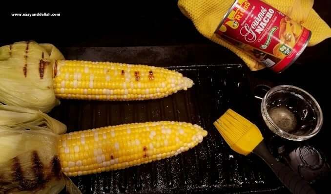 Two ears of corn on the cob on a grilling pan