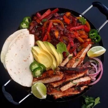 close up of pork fajitas with tortillas on the side