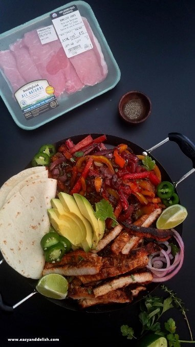 Pork fajita bowl served in a skillet with tortillas on the side.