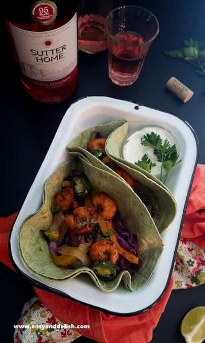Spicy taco shrimp fajitas served in tortillas with a bottle of wine at the background