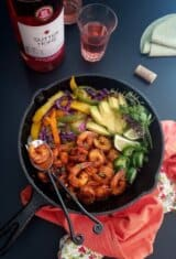 a skillet of shrimp fajitas with wine on the bachground
