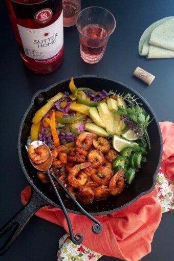 a skillet of shrimp fajitas with wine on the bachground