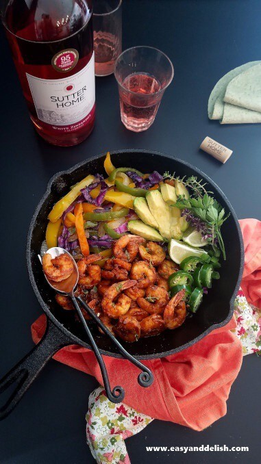 Spicy Taco Shrimp Fajitas in a skillet and a bottle of wine